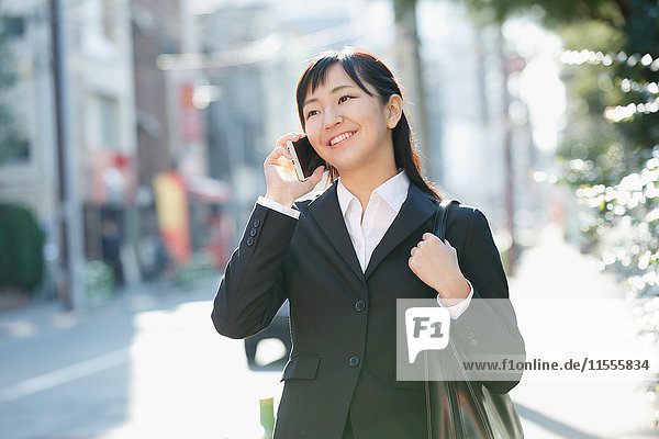 Japanese young businesswoman on the phone downtown Tokyo