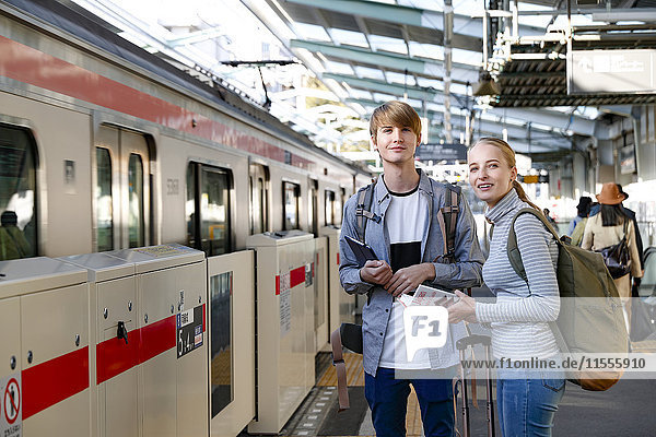 Caucasian tourist couple at train station  Tokyo  Japan