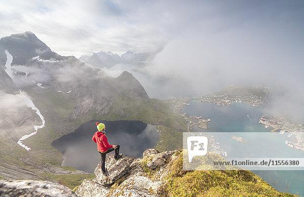 Hiker on summit admires the blue lake and sea framing the village  Reinebringen  Moskenesoya  Lofoten Islands  Norway  Scandinavia  Europe