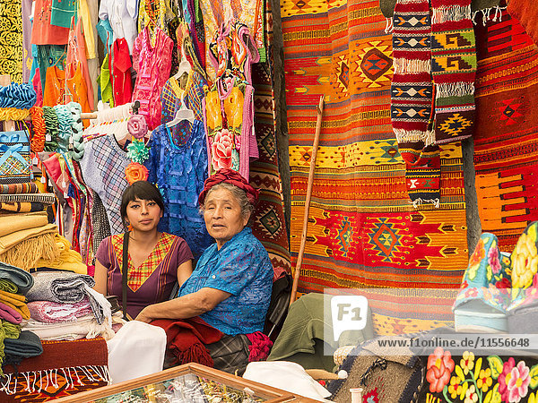 Women talking in market with background of handmade rugs and clothing  Oaxaca  Mexico  North America