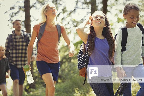 Lächelndes Familienwandern in sonnigen Wäldern