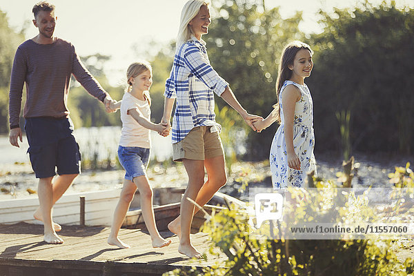 Barfuß-Familie hält sich an den Händen und geht auf dem Dock spazieren