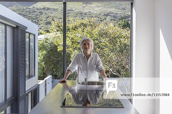 Portrait confident mature woman standing in modern home showcase interior kitchen