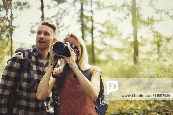 Paar Wandern und Fotografieren von Wäldern mit digitaler Spiegelreflexkamera
