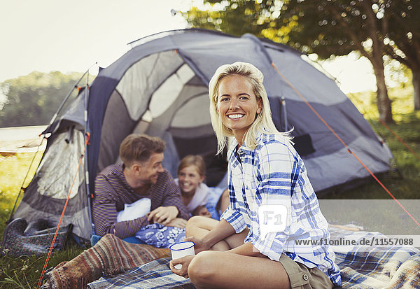 Portrait lächelnde Mutter beim Kaffeetrinken mit der Familie im Zelt auf dem Campingplatz