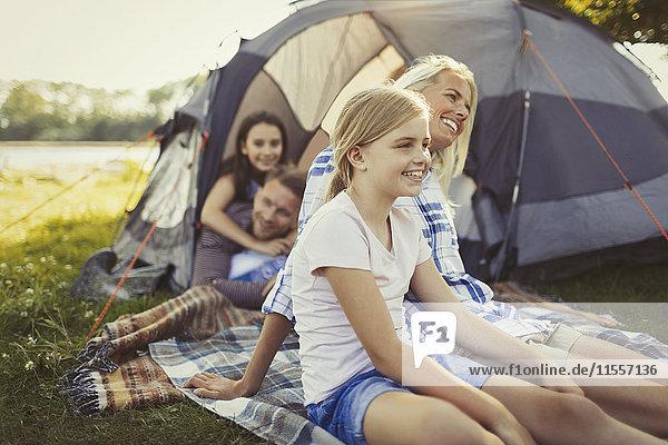 Lächelnde Familie entspannt vor dem Campingplatz-Zelt