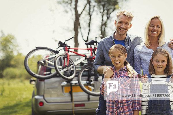 Portrait lächelnde Familie in der Nähe des Autos mit Mountainbikes