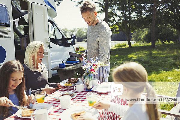 Familienfrühstück am Tisch vor dem sonnigen Wohnmobil
