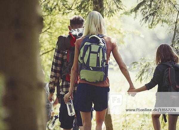 Mutter und Tochter mit Rucksäcken beim Wandern im Wald