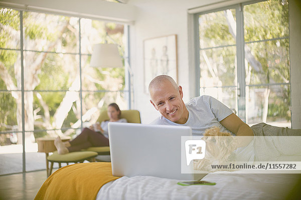 Smiling man with dog using laptop on bed