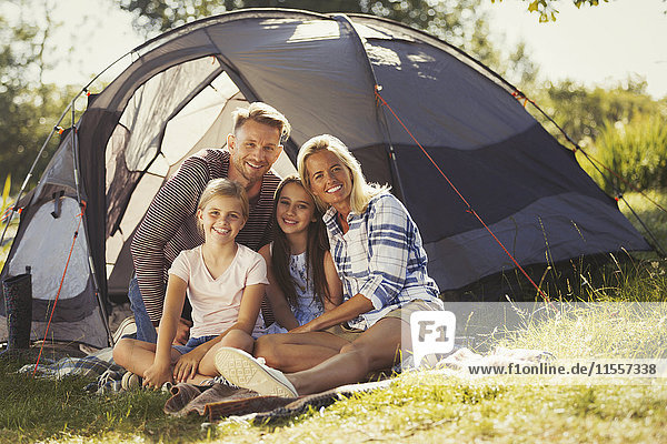 Portrait lächelnde Familie entspannt vor dem sonnigen Campingplatzzelt