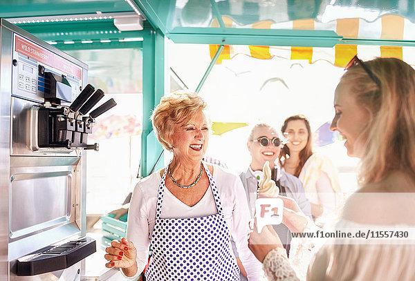 Lächelnde Seniorin  die der jungen Frau im Speisewagen Eis serviert.