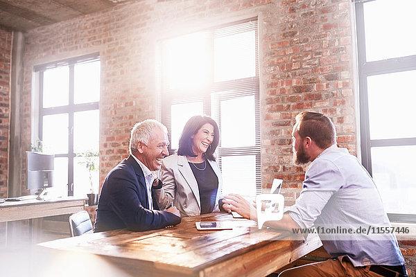 Lächelnde Geschäftsleute treffen sich am Tisch im Büro