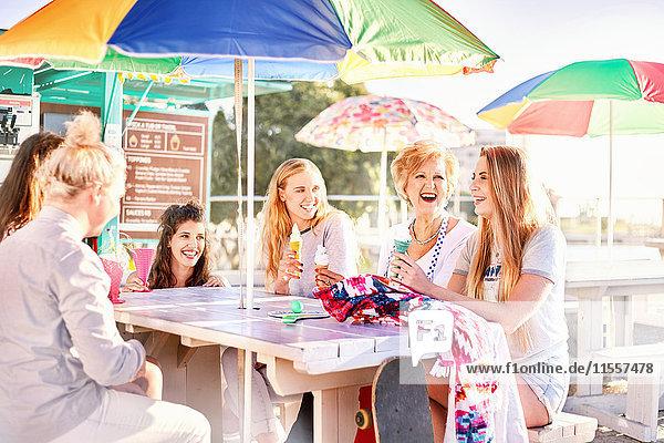 Glückliche Frauen essen Eis am sonnigen Promenaden-Picknicktisch