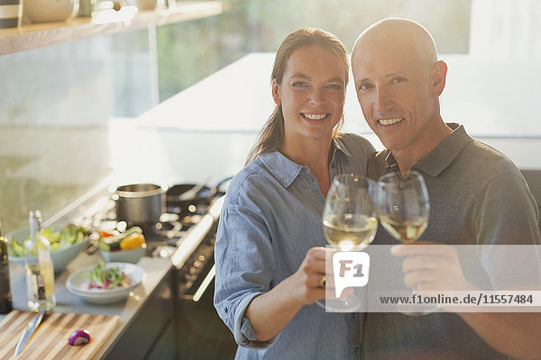 Portrait happy mature couple toasting white wine glasses  cooking in kitchen