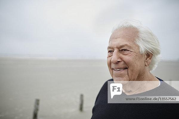 Lächelnder älterer Mann schaut weg am Strand