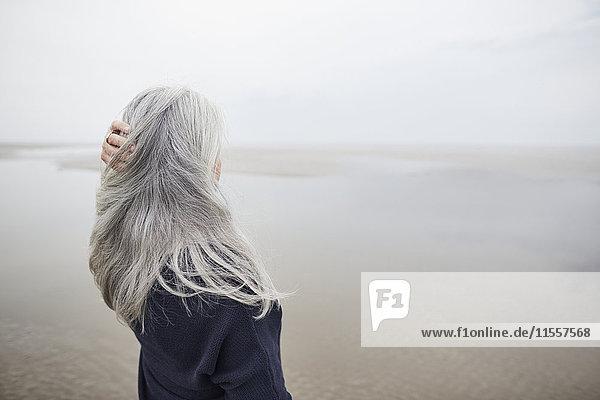 Seniorin mit Hand in langen grauen Haaren am Winterstrand