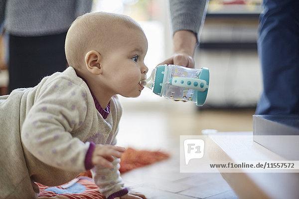 Kleines Mädchen krabbelt und trinkt aus dem Schluckbecher