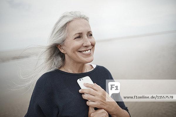 Lächelnde Seniorin mit Handy am Winterstrand
