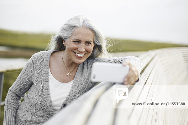 Lächelnde ältere Frau  die Selfie an der Strandpromenade nimmt.