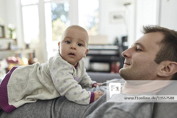 Portrait neugierige kleine Tochter auf der Brust des Vaters liegend