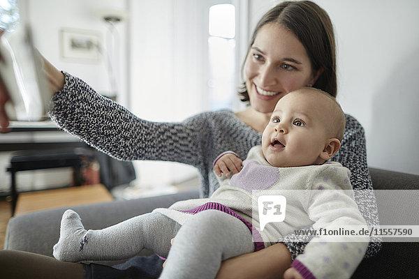 Lächelnde Mutter hält Baby-Tochter und nimmt Selfie mit Fotohandy mit.