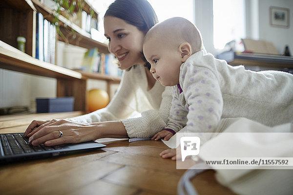 Baby Tochter beobachtet Mutter beim Tippen auf dem Laptop auf dem Boden