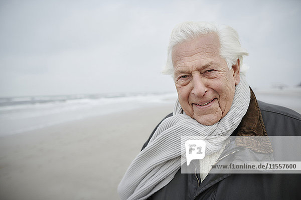 Porträt souveräner Senior mit Schal am Winterstrand
