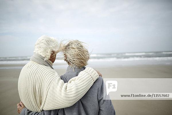 Nachdenkliches Seniorenpaar beim Umarmen und Blick aufs Meer am windigen Winterstrand