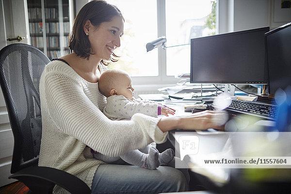 Lächelnde Mutter mit Baby-Tochter am Schreibtisch im Home-Office