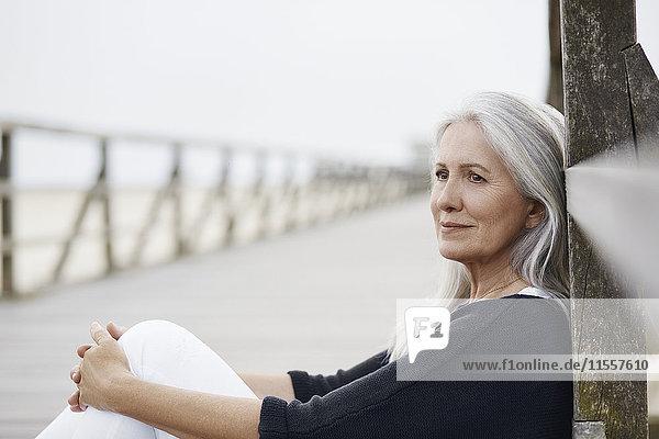 Nachdenkliche Seniorin entspannt sich an der Strandpromenade