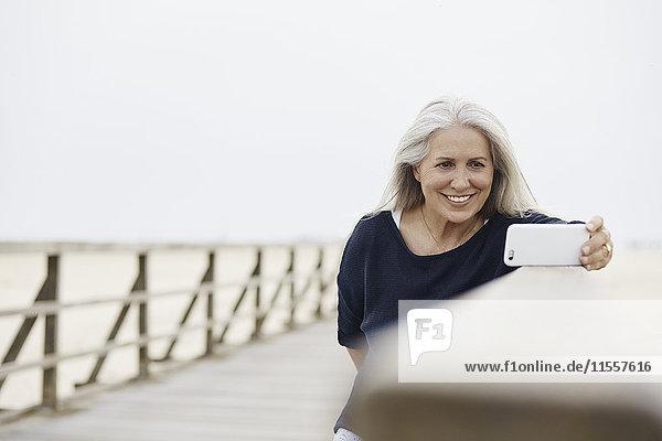 Lächelnde ältere Frau  die Selfie mit Fotohandy auf Strandpromenade nimmt