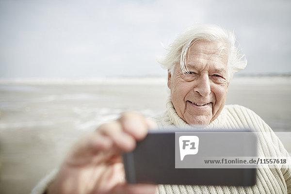 Lächelnder älterer Mann  der Selfie mit Handy am Strand nimmt