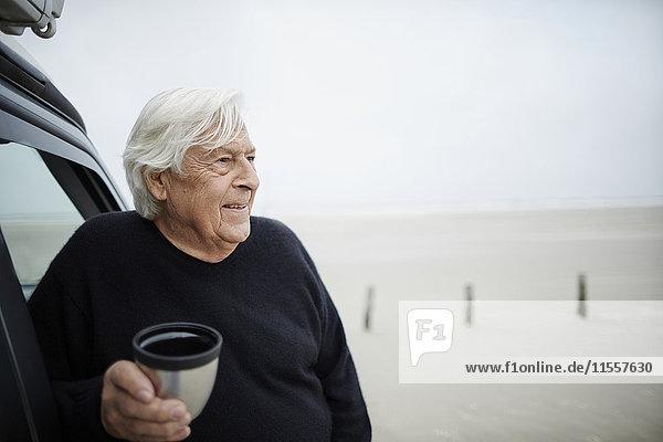 Fröhlicher älterer Mann trinkt Kaffee im Auto am Winterstrand