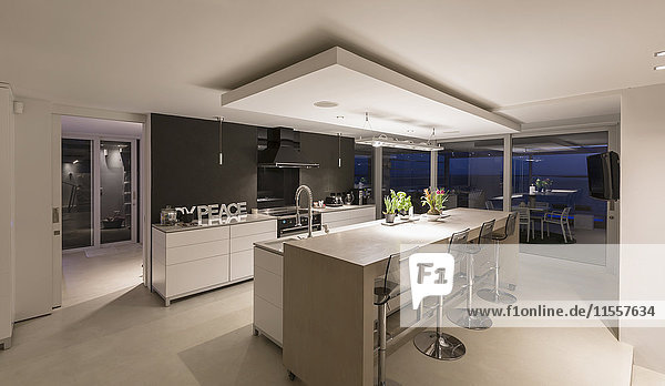 Illuminated modern luxury home showcase interior kitchen at night