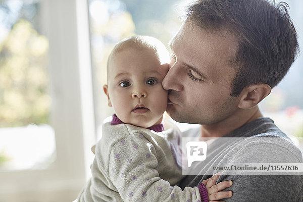 Portrait Baby Tochter wird von Vater auf die Wange geküsst