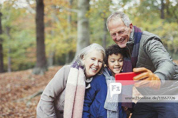 Großeltern und Enkel nehmen Selfie in den Herbstwäldern