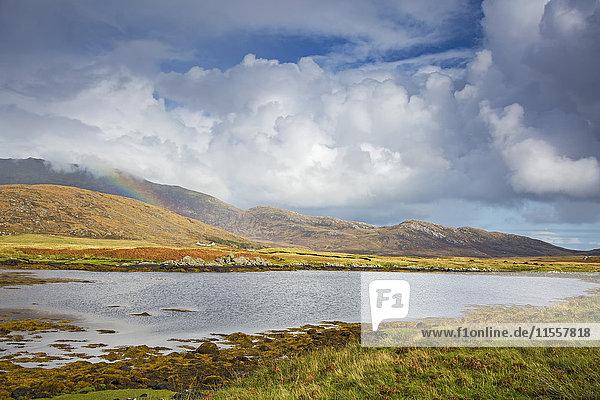 Ruhiger Blick auf Wolken und Regenbogen über sanfte Hügel jenseits des Sees  Loch Aineort  South Uist  Outer Hebrides