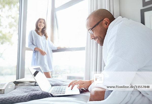 Lächelnde Frau beobachtet Freund im Bademantel beim Lesen Laptop im Bett
