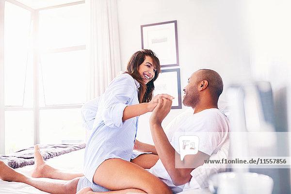 Lächelndes  verspieltes Paar auf dem Bett