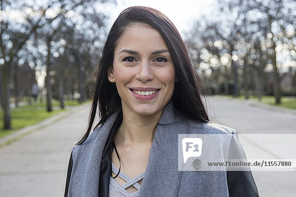 Porträt einer lächelnden jungen Frau mit Nasenpiercing im Park