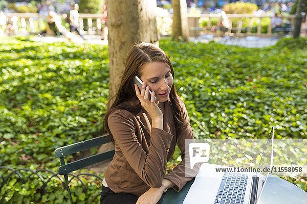 Junge Geschäftsfrau am Telefon sitzt am Tisch im Park mit Laptop