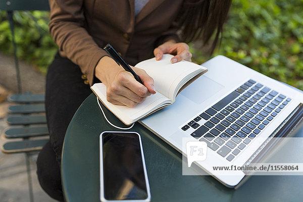 Junge Geschäftsfrau mit Laptop am Tisch im Park beim Notieren  Teilansicht
