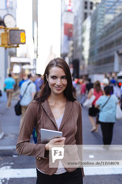 USA  New York  Manhattan  portrait of young businesswoman with tablet crossing the street