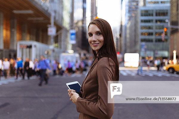 USA  New York  Manhattan  Portrait einer lächelnden jungen Geschäftsfrau mit Tablette auf der Straße