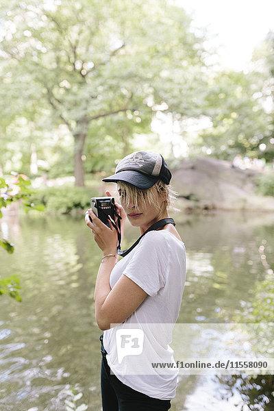 Junge Frau mit einer Vintage-Kamera beim Fotografieren im Park