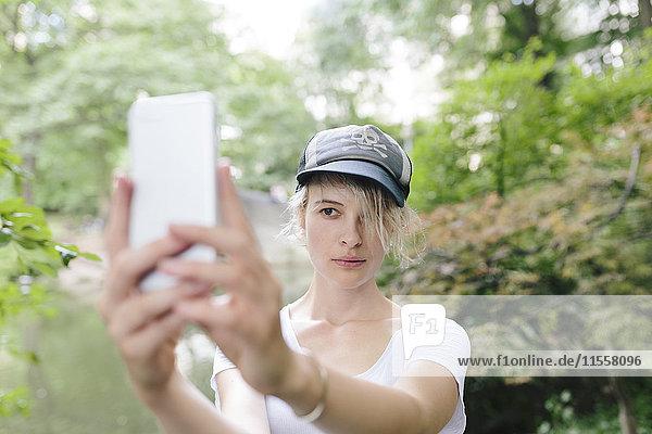 Junge Frau mit einem Selfie im Park