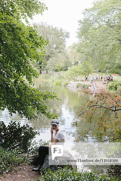 Junge Frau sitzt am Seeufer im Park und telefoniert mit dem Handy.
