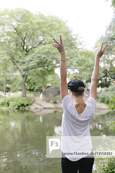 Rückansicht einer jungen Frau  die am Seeufer im Park mit erhobenen Armen steht.
