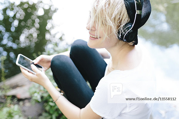Junge Frau sitzt am Seeufer im Park  trägt Kopfhörer und hält ein Handy.